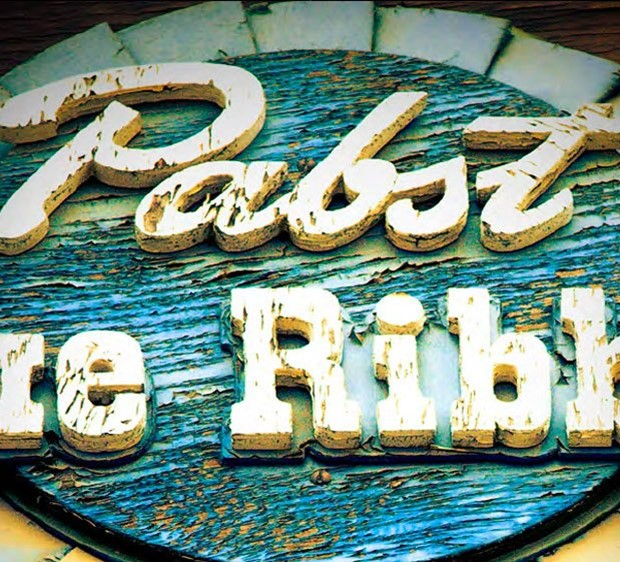 Closeup of a weathered, wooden Pabst Blue Ribbon sign.